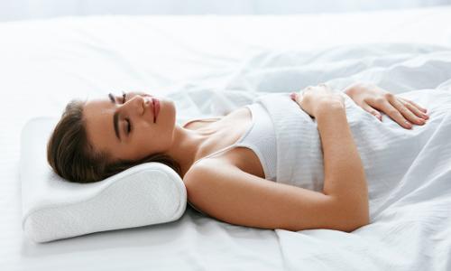 Frau schläft auf Nackenstützkissen